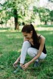 Atleta de la muchacha en una camiseta negra y pantalones blancos que atan cordones en las zapatillas de deporte foto de archivo