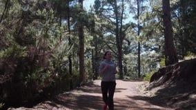 Atleta de la muchacha que corre en el bosque almacen de metraje de vídeo