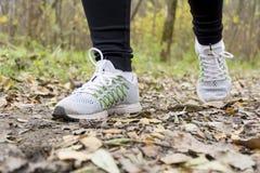 Atleta de la muchacha que corre en el parque a lo largo de la trayectoria en otoño Fotos de archivo libres de regalías