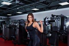 Atleta de la muchacha que hace ejercicios con un barbell Club de deporte Fotografía de archivo libre de regalías