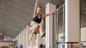 Atleta de la muchacha que realiza salto de longitud en salvadera almacen de video
