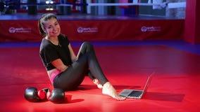 Atleta de la muchacha que se sienta en las esteras y la sonrisa