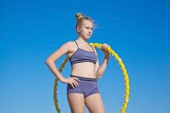 Atleta de la muchacha que sostiene el aro amarillo Imágenes de archivo libres de regalías