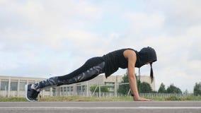 Atleta de la mujer joven de la aptitud que hace ejercicio del tablón en estadio fotografía de archivo libre de regalías