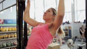 Atleta de la mujer joven levantado en la barra Muchacha hermosa y atlética que trabaja en sí misma, deportes y forma de vida sana almacen de video