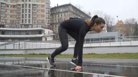 Atleta de la mujer joven que esprinta delante de cámara en una trayectoria del funcionamiento que corre la pista atlética 120fps almacen de metraje de vídeo