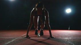 Atleta de la mujer profesional en los gotovtes de un fondo de la oscuridad para correr el sprint de zapatos que activan en zapati almacen de video