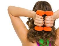 Atleta de la mujer que hace ejercicio con pesas de gimnasia. vista posterior Fotografía de archivo libre de regalías