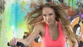 Atleta de la mujer que hace entrenamiento intenso en la bici del gimnasio almacen de metraje de vídeo