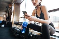 Atleta de la mujer que usa el teléfono celular en gimnasio Foto de archivo libre de regalías
