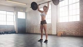Atleta de sexo femenino apto que hace la elevación del peso pesado Foto de archivo