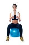 Atleta de sexo femenino atractivo que se sienta en bola azul Imágenes de archivo libres de regalías