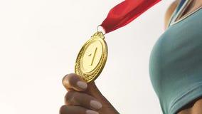 Atleta de sexo femenino Biracial que muestra la medalla de oro antes de cámara, de éxito y de la victoria metrajes