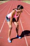Atleta de sexo femenino cansado que se coloca en pista corriente Imagen de archivo
