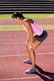 Atleta de sexo femenino cansado que se coloca en pista corriente Imágenes de archivo libres de regalías