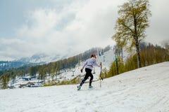 Atleta de sexo femenino con los polos del senderismo en las montañas nevosas del fondo Imágenes de archivo libres de regalías