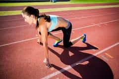 Atleta de sexo femenino confiado en listo a la posición de funcionamiento Fotografía de archivo
