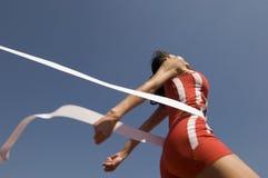 Atleta de sexo femenino Crossing Finish Line contra el cielo azul Foto de archivo
