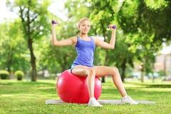 Atleta de sexo femenino en un parque que se sienta en una bola y que ejercita con d Fotos de archivo libres de regalías