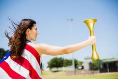 Atleta de sexo femenino envuelto en antorcha del fuego de tenencia de la bandera americana Imagen de archivo