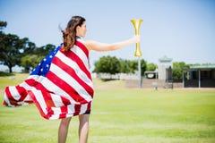 Atleta de sexo femenino envuelto en antorcha del fuego de tenencia de la bandera americana Fotografía de archivo
