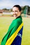 Atleta de sexo femenino envuelto en bandera brasileña Fotografía de archivo libre de regalías
