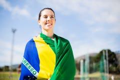 Atleta de sexo femenino envuelto en bandera brasileña Fotos de archivo