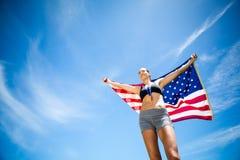 Atleta de sexo femenino feliz que soporta la bandera americana Imagen de archivo libre de regalías