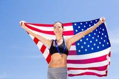 Atleta de sexo femenino feliz que soporta la bandera americana Imagenes de archivo