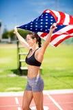Atleta de sexo femenino feliz que soporta la bandera americana en pista corriente Foto de archivo