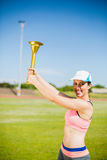 Atleta de sexo femenino feliz que sostiene una antorcha del fuego Foto de archivo libre de regalías