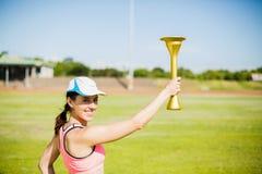 Atleta de sexo femenino feliz que sostiene una antorcha del fuego Imagen de archivo