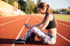 Atleta de sexo femenino feliz que usa el teléfono móvil en pista corriente Imagen de archivo libre de regalías