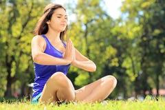 Atleta de sexo femenino joven en la ropa de deportes que hace ejercicio de la yoga asentado encendido Imagen de archivo