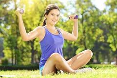 Atleta de sexo femenino joven en ropa de deportes que ejercita con pesas de gimnasia adentro Imágenes de archivo libres de regalías