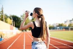 Atleta de sexo femenino joven que bebe de la botella de agua después de entrenamiento al aire libre Fotografía de archivo libre de regalías