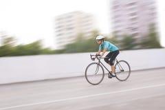 Atleta de sexo femenino joven que compite con en una bici. imagen borrosa de movimiento Fotografía de archivo