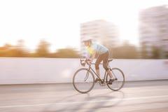 Atleta de sexo femenino joven que compite con en una bici. imagen borrosa de movimiento Foto de archivo