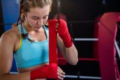 Atleta de sexo femenino joven que envuelve el vendaje rojo a mano fotografía de archivo libre de regalías
