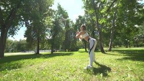 Atleta de sexo femenino joven que hace ejercicios agazapados al aire libre en parque Muchacha apta que resuelve su base y glutes  metrajes