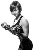 Atleta de sexo femenino joven que hace rizos de la pesa de gimnasia Imagen de archivo