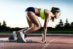 Atleta de sexo femenino joven que lanza de la línea del comienzo en una raza fotografía de archivo libre de regalías
