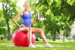 Atleta de sexo femenino joven que se sienta en la bola de la aptitud que sostiene una botella adentro Imagen de archivo