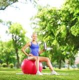 Atleta de sexo femenino joven que se sienta en la bola de los pilates que sostiene una botella adentro Foto de archivo