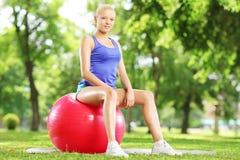 Atleta de sexo femenino joven que se sienta en una bola de la aptitud en parque Foto de archivo libre de regalías