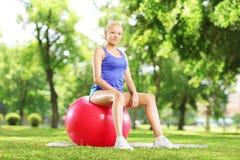 Atleta de sexo femenino joven que se sienta en una bola de los pilates en parque Imágenes de archivo libres de regalías