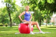 Atleta de sexo femenino joven que se sienta en una bola de los pilates y que mira c Imagen de archivo libre de regalías