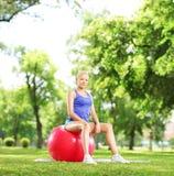 Atleta de sexo femenino joven que se sienta en una bola de los pilates y que mira el Ca Foto de archivo