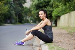 Atleta de sexo femenino joven que sienta al aire libre la reclinación después de entrenamiento Imagen de archivo