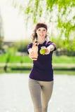 Atleta de sexo femenino lindo joven en un chaleco azul que sostiene una botella de agua y de una manzana y que mira la cámara Fotografía de archivo libre de regalías